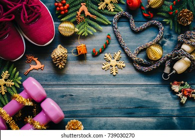 Exercise, Fitness and Working Out Merry Christmas and Happy new year concept, dumbbells, sport shoes, skipping rope or jump rope  in heart shape with Christmas decoration items on wood background.