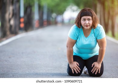 Exercise and healthy concept : Fat woman feeling tired while running in the park