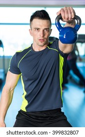 Exercise With Kettle Bell. Athletic man doing exercises with blue kettle bell. Model posing