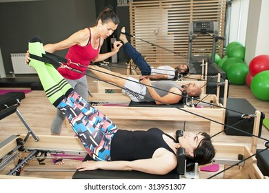 Exercise on pilates device reformer with instructor at gym