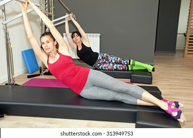 Exercise on pilates wall unit at gym