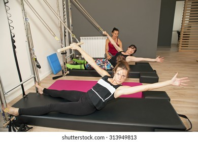 Exercise on pilates wall unit with instructor at gym