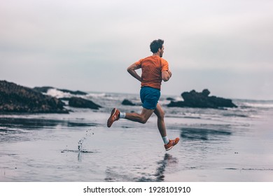 Exercise outdoor athlete man running on wet sand at beach training cardio sprinting fast. Profile of runner in sportswear clothes jogging.
