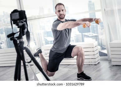 Exercise program. Positive charming male blogger using weights while squatting and recording video