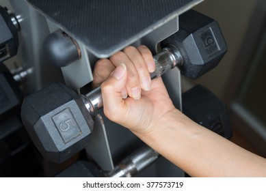 Exercise series : Woman's hand picking up dumbbell