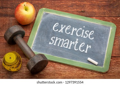 exercise smarter - white chalk text on a slate blackboard against weathered red painted barn wood with a dumbbell, apple and tape measure