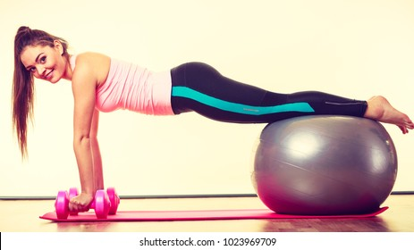 Exercise sport fitness health concept. Fit girl exercising. Attractive female warming up with ball and dumb bell weights.