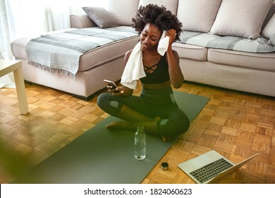 Exercise staying home woman watching fitness videos online on mobile phone yoga workout live streaming influencer fit girl working out in living room of apartment house.