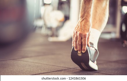 Exercise for the whole body. Senior man stretching and working exercise for leg. Close up.