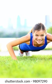Exercise woman doing push ups in outdoor workout training. Asian sport fitness woman smiling cheerful and happy looking at camera.
