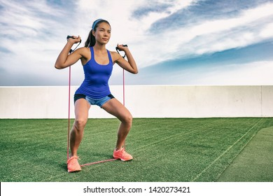 Exercise woman with fitness elastic band workout in outdoor gym . Asian girl doing resistance training outside on grass. Fit people lifestyle. Squat and shoulder press with elastics.