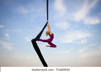 exercises with aerial silk outdoor, sky background. beautiful fit woman training acrobatic in air.