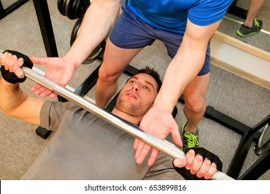Exercises for the breasts with barbell in the gym. Good looking young man doing bench presses while getting help from his personal trainer and spotter. Sport, fitness, healthy lifestyle, gym concept.
