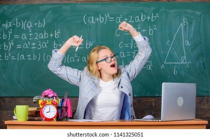 Exercises to maintain vivacity. Teacher woman sit table classroom chalkboard background. Work far beyond actual school day. Stretch and do exercises to increase vivacity and get energy charge.