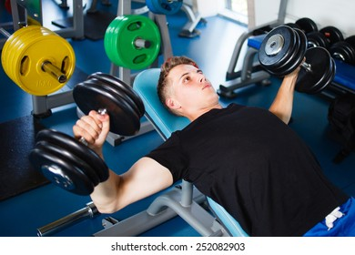 Exercising with dumbbells at gym.