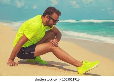 Exercising injury on a tropical sandy beach near sea / ocean.