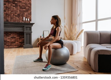 Exercising on ball. Young slim and fit businesswoman exercising on fitness ball at home in the morning
