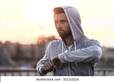 Exercising on fresh air. Confident young man stretching his body before running while standing outdoors