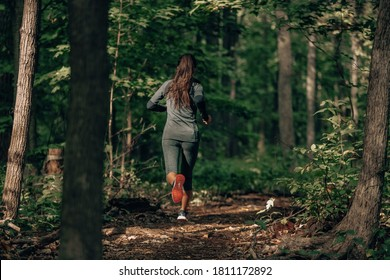 Exercising outdoors is healthy for active lifestyle runners. Autumn trail run woman running in nature from behind in dark forest. Outdoor jog. - Shutterstock ID 1811172892