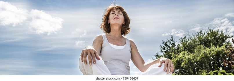 exercising outside - radiant 50s yoga woman sitting on a stone, seeking for spiritual balance with tree background,low angle view, long banner