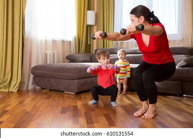 Exercising together. Happy mother and son exercising with dumbbells and smiling while standing in home.