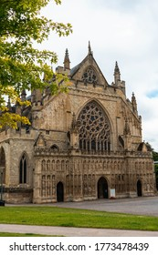 Exeter Cathedral side on image with cloudy sky in the background and framed by green trees and grass in the foreground