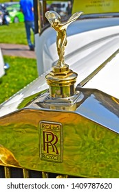 Exeter, Devon / England - 5/10/2019: Classic car show. The Spirit of Ecstasy is the name given to the flying lady emblem on top of the radiator bonnet on a Rolls Royce. This is a gold version.