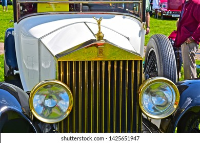 Exeter, Devon / England - 5/10/2019: Classic car show. Front radiator / grille & headlamps of vintage Rolls Royce. Details such as the Spirit of Ecstasy are finished in gold! White bodywork.