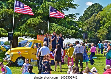 Exeter, Devon / England - 5/10/2019: 'The Liberty Sisters' vocal trio performing American hits from 1920s-30s on back of Classic GMC tow truck at  Classic Car Show.People dancing/ watching.