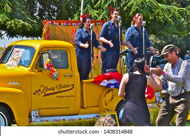 Exeter, Devon / England - 5/10/2019: 'The Liberty Sisters' vocal trio performing American hits from 1920s-30s,Performing on back of Classic GMC tow truck at  Classic Car Show.People dancing/ watching.