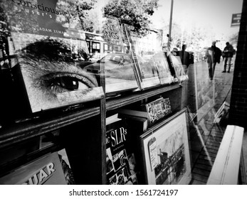 EXETER, DEVON, UK - November 16 2019: Black and white photo, focus on foreground detail, large human eye on book jacket in charity shop window, reflections of busy shopping street and distant people.