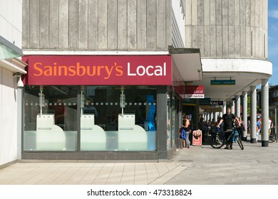 Exeter, Devon, United Kingdom - August 23, 2016: People pass by Sainsbury's Local store on High street. J Sainsbury plc has over 1200 supermarkets and convenience stores.