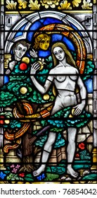 Exeter, England - Dec 04, 2017: Stained Glass in Exeter Cathedral, Lady Chapel Window Lower Panel, Adam and Eve with the Snake in the Garden of Eden