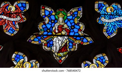 Exeter, England - Dec 04, 2017: Stained Glass in Exeter Cathedral, West Window Tracery Light, Jesus on the Throne in Heaven Surrounded by Angels