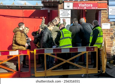 EXETER, ENGLAND - FEBRUARY 21, 2015: Security guards search Plymouth Argyle football fans during the police operation at the League 2 football match between Exeter City FC and Plymouth Argyle FC