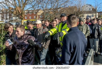 EXETER, ENGLAND - FEBRUARY 21, 2015: Police officer pushes a Plymouth Argyle football fan during the police operation at the League 2 football match between Exeter City FC and Plymouth Argyle FC