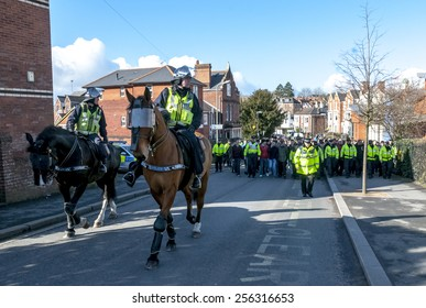 EXETER, ENGLAND - FEBRUARY 21, 2015: Devon and Cornwall Police escort Plymouth football fans during the police operation at the League 2 football match between Exeter City FC and Plymouth Argyle FC