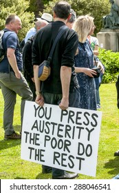 """EXETER, ENGLAND - JUNE 13, 2015: Man holding a placard, which says """"You Press Austerity The Poor Do The Rest"""" at the Devon 'End Austerity NOW!' Rally in Exeter on June13th, 2015 in Exeter, UK"""
