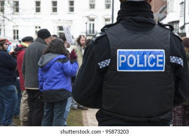 EXETER - FEBRUARY 11: A Devon & Corwall policeman watches the Occupy Exeter activists as they celebrate their achievments during leaving the green event in Exeter  on February 11, 2012 in Exeter, UK