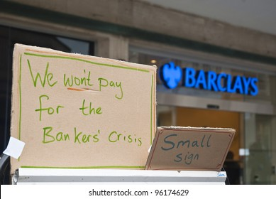 """EXETER - FEBRUARY 11: A sign saying """"We won't pay for the bankers crisis"""" in front of the Exeter branch of Barclays bank on February 11, 2012 in Exeter, UK."""
