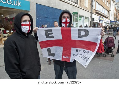 EXETER - FEBRUARY 12: Exeter English Defence League members hold up their EDL St George flag during the EDL's small gathering in Exeter City Centre  on February 12, 2011 in Exeter, UK.