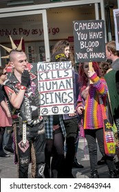 """EXETER - JULY 8: A man holds a placard which says """"Austerity Kils Human Beings"""" at the Exeter Budget Day Action #AusterityKills in Exeter City Centre on july 8th, 2015 in Bedford Square, Exeter, UK"""