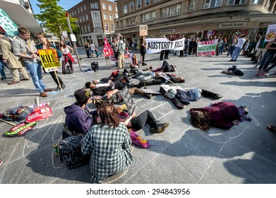 EXETER - JULY 8: Protesters play dead & hold up placards during the Exeter Budget Day Action #AusterityKills in Exeter City Centre on july 8th, 2015 in Bedford Square, Exeter, UK