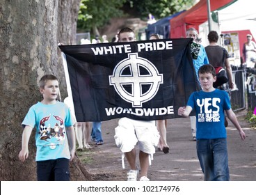 EXETER - JUNE 4: Man displaying a White Pride World-Wide flag, walks through Exeter Festival  on June 4, 2011 in Exeter, UK. (NOTE: THE TWO CHILDREN ARE NOT ASSOCIATED WITH THIS FLAG OR FLAG HOLDER.)