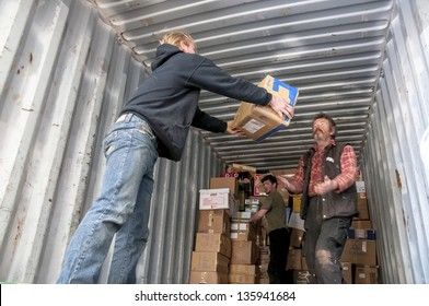 EXETER - MARCH 14: Members and volunteers from BookCycle UK carry boxes of books and load them onto the container bound for Ghana at the Bookcycle UK warehouse on March 14, 2013 in Exeter, Devon, UK