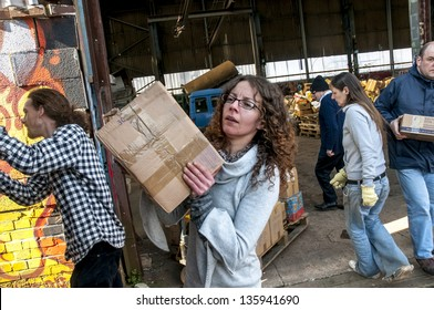 EXETER - MARCH 14: Sakeenah Feghir from BookCycle UK carring a box of books and loading them onto the container bound for Ghana at the Bookcycle UK warehouse on March 14, 2013 in Exeter, Devon, UK