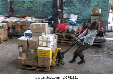 EXETER - MARCH 14: Sakeenah Feghir from BookCycle UK pulling a pallet of books to the container bound for Ghana at the Bookcycle UK warehouse on March 14, 2013 in Exeter, Devon, UK