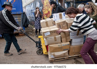 EXETER - MARCH 9: Volunteer from BookCycle move a pallet of boxed books to the container that is taking donated book to Ghana on March 9,  2012 in Exeter.