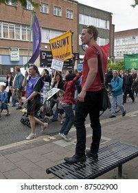 EXETER - MAY 2: Young man urges on the protesters as they in Exeter City as part of the May Day demonstration against the coalition governments spending cuts  on May 2, 2011 in Exeter.