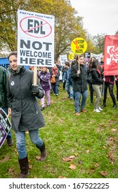 EXETER - NOVEMBER 16: A lady holds up a 'EDL Not Welcome Here', with a stop the Nazis sign behind her during the Exeter Together march and diversity festival on November 16, 2013 in Exeter, Devon, UK
